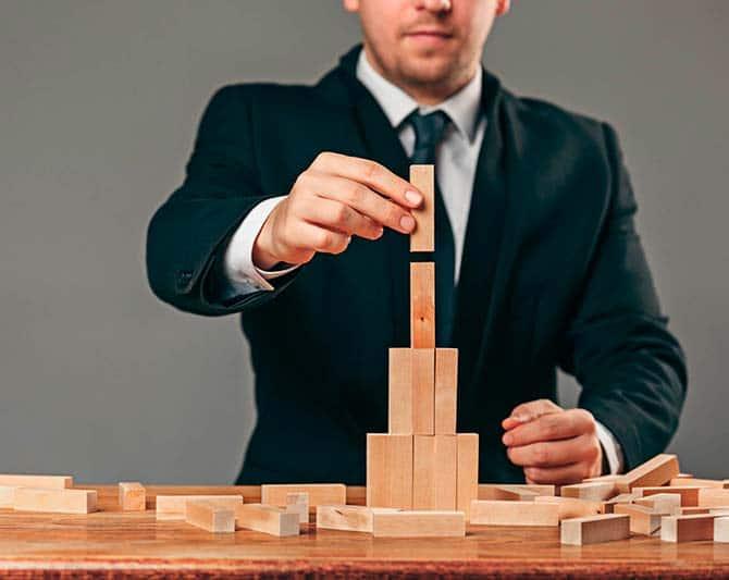 Imagen de ejecutivo construyento una torre de bloques de madera